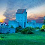 Visbyn linnan muuri, vihreä nurmi ja taivas auringonnousun aikaan.
