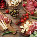 Leikkeleitä, juustoja, oliiveja, tomaatteja ym. antipastolajitelmassa puisella pöydällä.