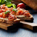 Tomaattitäytteisiä bruschetta-leipiä puisella leikkuulaudalla.