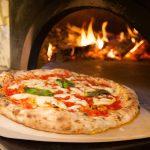 Pizza pizzalapion päällä puilla lämpiävän uunin edustalla.