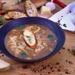 Sipulikeittoa vadissa, päällä leipäpala ja yrttejä. Ympärillä juustoa, sipuleita, mausteita ym. puisella tasolla.