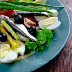 Anjovista ja kananmunia salaattilautasella.