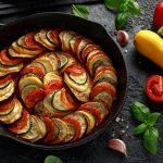 Kasvispannu ylhäältä päin kuvattuna, ympärillä kurpitsoja, tomaatteja, valkosipulin kynsiä ja basilikaa.