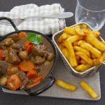 Lihapataa kauhallisessa vadissa, vieressä kori, jossa ranskalaisia.
