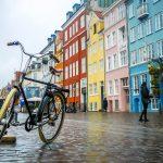 Vanha pyörä Kööpenhaminan kadulla värikkäiden rakennusten edustalla.