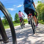 Ryhmä pyöräilijöitä etenemässä tiellä kesäisenä päivänä.