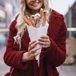 Hymyilevällä naisella käsissään annos churroja pahvikartiossa.