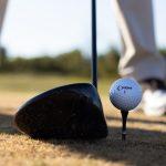 Henkilö lyömässä golfpalloa