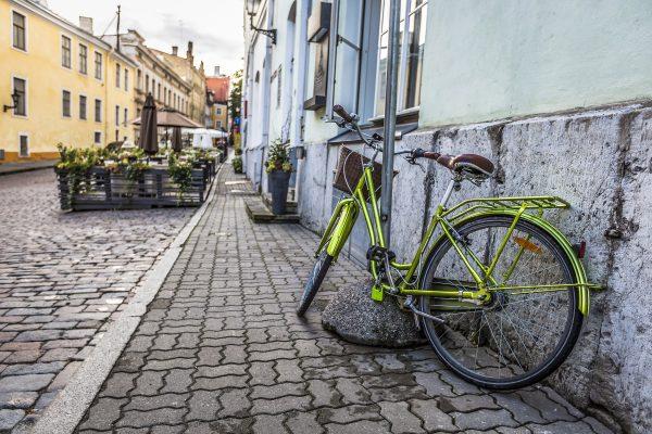 Vihreä pyörä nojaa rakennuksen seinään Tallinnan vanhan kaupungin kadulla.
