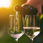 Käsi kaataa pullosta valkoviiniä laseihin