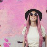 Pinkkihiuksinen nainen pinkin seinän edessä