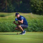 Mies tuulettaa golflyöntiä greenillä