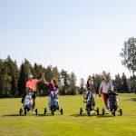 Neljä golfaria greenillä kärryjen kanssa