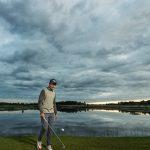 Mies golfkentällä veden äärellä