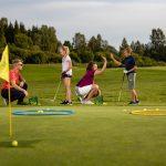 Lapsia ja aikuisia golfaamassa