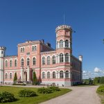 Kaunis vaaleanpunainen linnarakennus puiston keskellä kirkkaana kesäpäivänä.