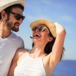 Iloinen pariskunta hatut ja aurinkolasit päässään, taustalla meri.