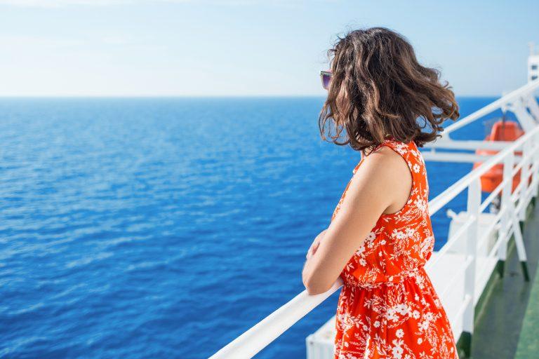Punavalkoiseen kukkamekkoon pukeutunut nainen katselee merta laivan kannelta.