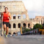 Punapaitainen mies juoksemassa kadulla, taustalla Colosseum.