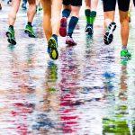 Juoksijoita märällä tiellä, värikkäät asut heijastuvat veden pintaan.