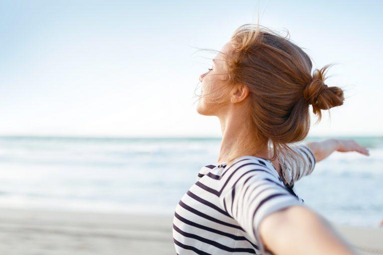 Raitapaitainen nainen levittää käsiään rannalla.