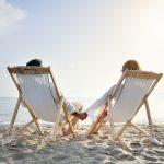 Pariskunta kansituoleissa hiekkarannalla.