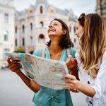 Kaksi nuorta naista nauraa ja katsoo karttaa kadulla.