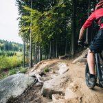Punatakkinen maastopyöräilijä polulla kivisellä rinteellä.