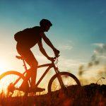 Maastopyöräilijän siluetti auringonlaskua vasten.