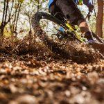 Maastopyöräilijä kääntyy vauhdikkaasti mutkassa metsäpolulla.