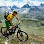 Maastopyöräilijä polulla rinteessä jylhissä vuoristomaisemissa.