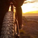 Lähikuva maastopyörän takarenkaasta, pyöräilijä pysähtyneenä ihailemaan auringonlaskua.