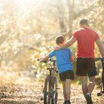 Isä ja poika taluttaa maastopyöriä metsätiellä, isä pitää kättä pojan olkapäällä.