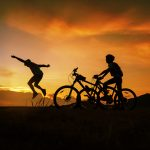 Kaksi pyöräilijää auringonlaskua vasten, toinen hyppäämässä ilmaan.