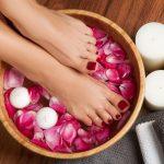 Lähikuva jaloista puisessa kylpyastiassa, kylpyveden pinnalla kelluu ruusun terälehtiä ja kynttilöitä.
