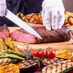 Puolikypsän lihapalan leikkaamista pöydällä, joka on täynnä herkullisen näköisiä kasviksia.
