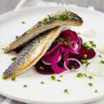 Lautaselle koostettu kala-annos, jossa paistettua kalaa ruohosipulia ja punajuurta