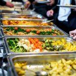 Ihmiset kokoavat lautasilleen buffetpöydän ruokavalikoimasta annoksia