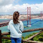 Farkkuasuinen nuori nainen katselee siltaa.